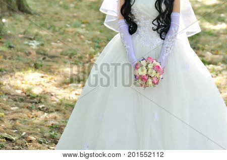 Bride holding colorful bouquet with her hands on wedding day