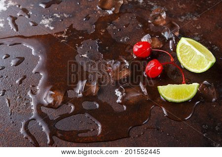 Lime pieces, maraschino cherry and melting ice cubes on brown marbled table background, copy space