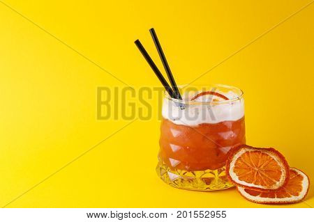 Cocktail on juicy orange background. Citrus alcohol beverage with tequila, blood orange juice and ginger beer, served with citrons and straws, copy space