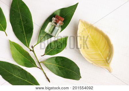 Laurel bay oil in bottle and ceramic plate with fresh green aroma leaves, top view white wooden table.