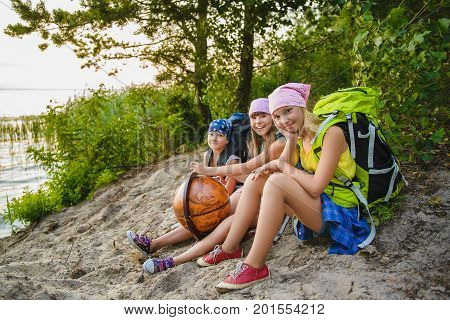 Teenager travelers with backpacks sitting on coast. Wanderlust travel concept.