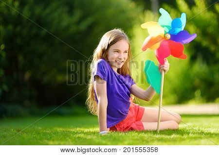 Adorable Little Girl Holding Colorful Toy Pinwheel On Sunny Summer Day