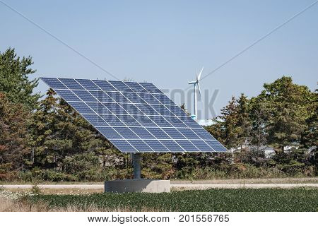 Two forms of renewable energy - solar panels and wind turbines.