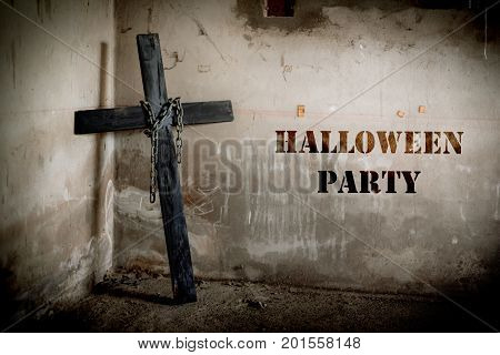 Black cross against the wall with hanging steel chain Halloween party festival posture advertising. Halloween's Day and ghost concept. Dark and scary tone tone pinterest and instragram like process.