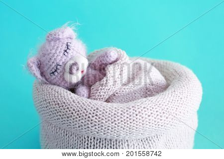 Cute handmade toy bear sleeping in knitted bag on color background