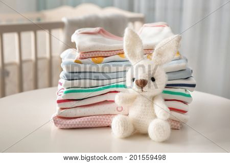 Knitted toy bunny and baby clothes on table