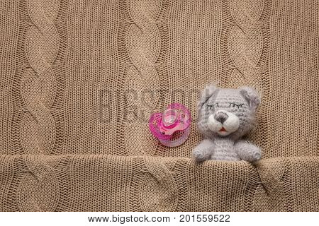 Cute handmade toy bear and soother on knitted background