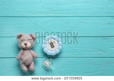 Composition with baby toy and accessories on wooden background