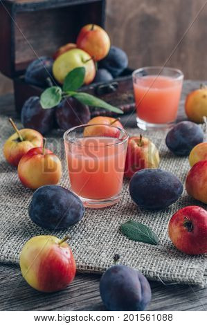 Fresh plum juice. The juice in the glass is surrounded by plums and apples on a wooden table. Still Life with Plums.