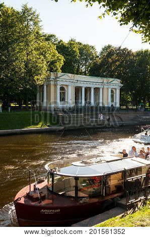 ST PETERSBURG RUSSIA - AUGUST 15 2017. Rossi Pavilion in the Michael Garden and the Moika river with pleasure boats in St Petersburg Russia. St Petersburg Russia city landscape
