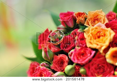 two golden wedding rings on floral background
