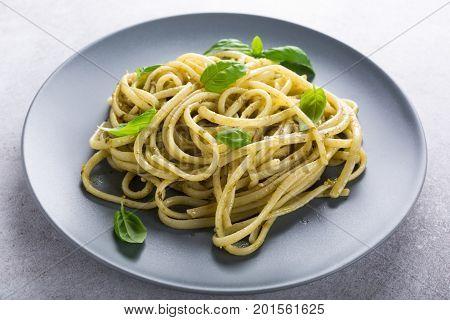 Homemade pasta, spaghetti, linguine with green pesto and basil. Italian healthy food concept.