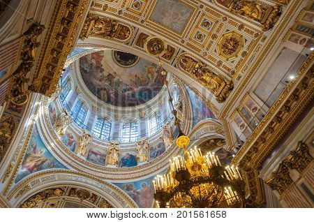 SAINT PETERSBURG RUSSIA - AUGUST 15 2017. Ceiling ornated with sculptures and Bible paintings in the interior of the Saint Isaac Cathedral in Saint Petersburg Russia. Saint Petersburg Russia landmark interior