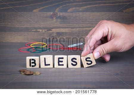 Bless. Wooden letters on dark texture background
