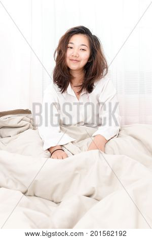 Beautiful woman waking up in her bed in the bedroom she is smiling after wake up.