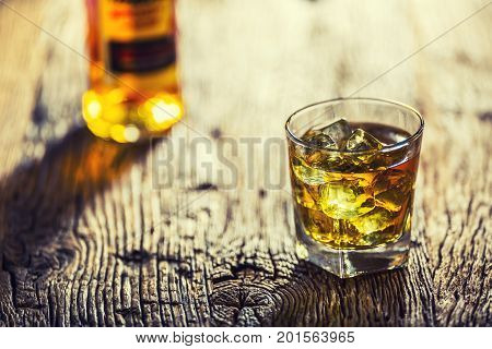 Whiskey. Whiskey Drink With Ice Cubes On Old Rustic Oak Table