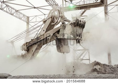 Big bucket powerful excavator work in the hot dusty fog of mining industry. Heavy industry background.