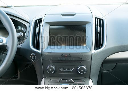 Car inside driver place. Interior of prestige modern car. Steering wheel, dashboard, display climate control. Black cockpit with wood metal decoration ambient light on isolated white background.