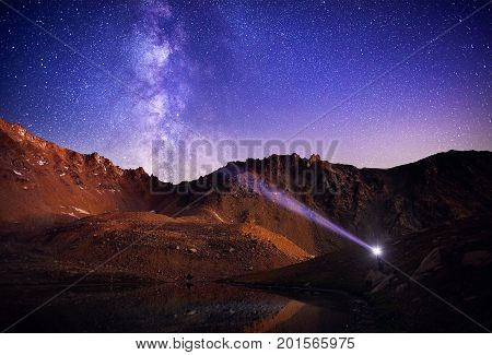 Man With Headlight In The Mountains At Night Sky