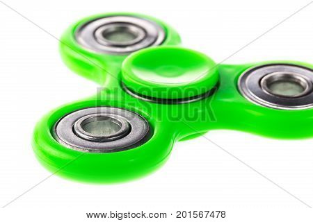 Green fidget spinner close up stress relieving toy isolated on white background