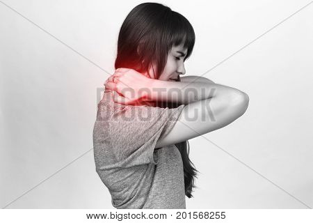 Portrait of a pretty woman holding her neck in pain and discomfort standing over gray background black and white with red accent