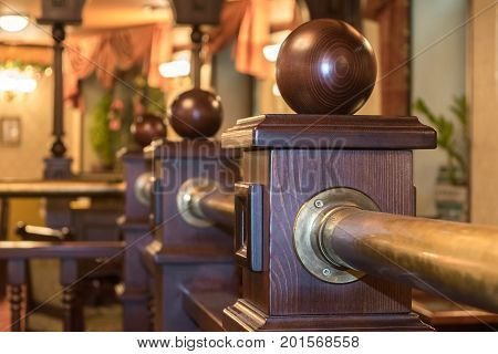 A fragment of a wooden fence in the interior of the restaurant or cafe. The fence posts with wooden balls. In the background is a cozy and comfortable interior with lamps and curtains.