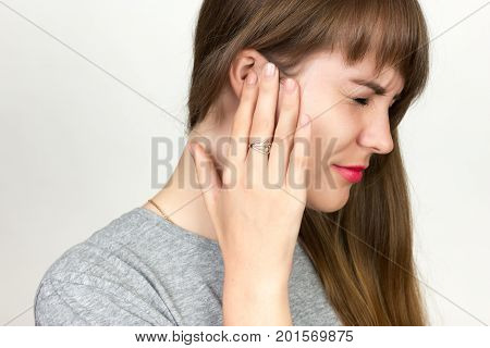 Young woman has a sore ear. girl suffering from otitis closeup over gray background