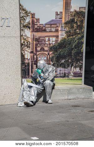 SYDNEY,NSW,AUSTRALIA-NOVEMBER 20,2016: Street artist resting on sidewalk in metallic, silver costume reading a book at the Circular Quay in Sydney, Australia