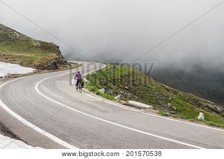 Woman on a bike travel on the most famous and dangerous road in Europe is a Transfagarasan road in Carpathian mountains Romania.