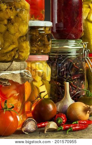 Jars with variety of pickled vegetables. Carrots field garlic parsley in glas. Preserved food. Fermented preserved vegetarian food concept
