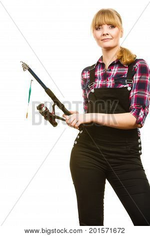 Fishing concept. Attractive woman in dungarees pink check shirt holding rod. Isolated background