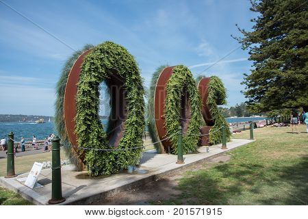 SYDNEY,NSW,AUSTRALIA-NOVEMBER 20,2016: Plant sign representing the 200 year anniversary at the Royal Botanic Gardens with tourists and boats in Farm Cove in Sydney, Australia.