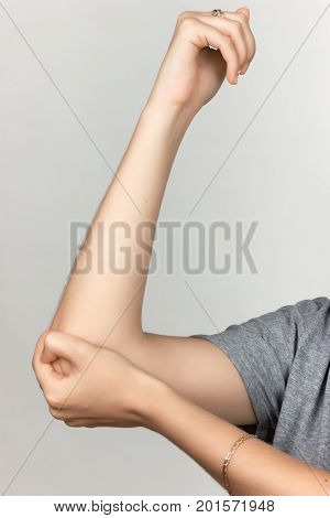 Elbow pain. Beautiful female holding her elbow over gray background