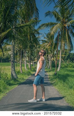Man standing in the middle of an empty road with palm trees.