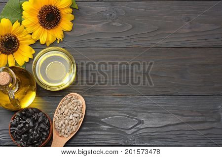 Sunflower oil in glass jug , seeds and flower on dark grey wooden background. top view with copy space