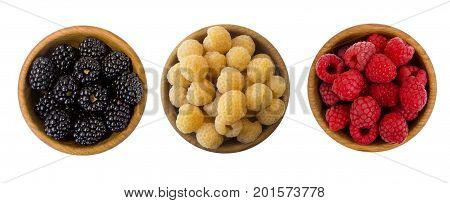 Black red and yellow berry in a wooden bowl isolated on white background. Raspberries and blackberries on white. Vegetarian or healthy eating. Juicy and delicious berries with copy space for text. Top view.
