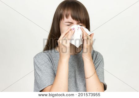 Portrait of a pretty woman having flu. girl blowing nose standing over gray background. Black and white with red accent.