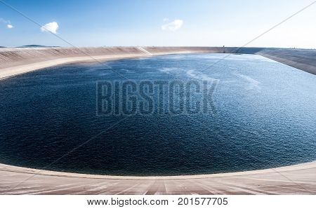 elevated reservoir of Dlouhe Strane hydro power plant on Dlouhe Strane hill in Jeseniky mountains above Kouty nad Desnou in Czech republic during morning with blue sky and only few small clouds