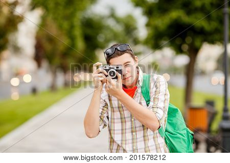 Photo of brunet with camera in summer on street in afternoon at city