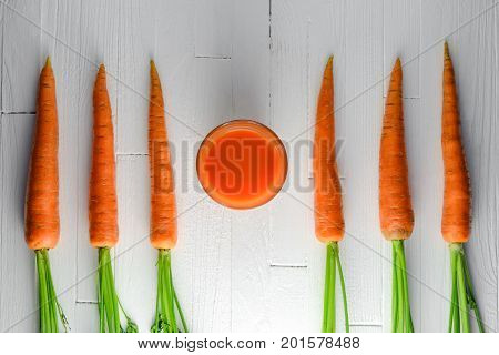 Healthy carrot smoothie in a jar with carrots on white wooden table top view. Healthy food background concept