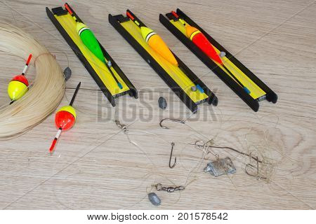 Fishing tackle - fishing spinning hooks and lures on light wooden background. fishing tackle on the table