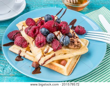 Homemade waffles with raspberries and blueberry on blue plate.