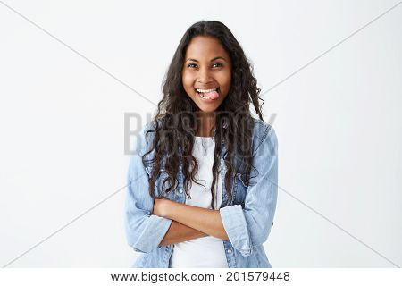 Funny dark-skinned female with loose black hair and charming dark eyes having joy while showing tongue, keeping her arms folded. Cheerful female student wearing denim shirt having fun after classes looking and showing tongue at the camera.