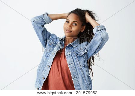 Fashionable young dark-skinned woman wearing denim jacket and red casual t-shirt tying her beautiful dak wavy hair while posing. Horizontal studio shot