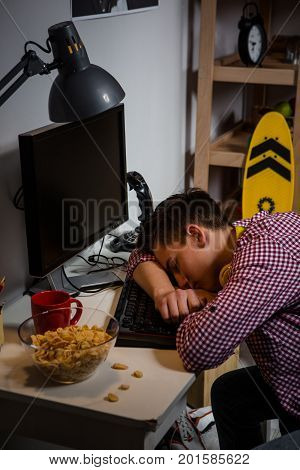 Teenage boy tired falling asleep at computer table. Problem of modern teenagers using computers too much.