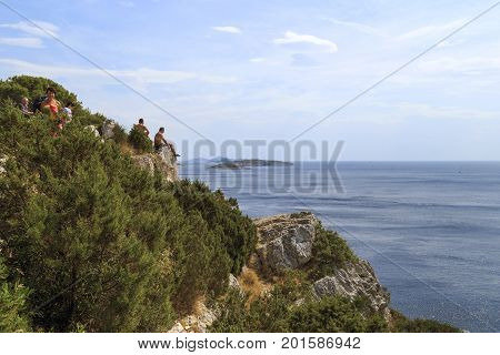 DUGI OTOK, CROATIA - SEPTEMBER 7, 2016: Unknown tourists sit on steep coastal cliffs of the island in Telascica Nature Park.