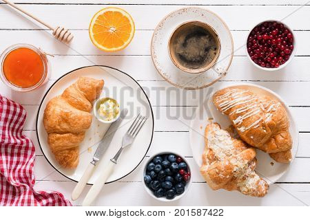 Fresh croissants with butter, jam, cup of coffee, fruits and berries on white table top view. Continental breakfast
