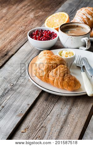 Fresh croissant, cup of coffee, orange, berries on rustic wooden table. Angle view and copy space. Continental breakfast