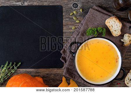 Pumpkin cream soup bowl on wooden table and blank chalk board for text recipe. Top view