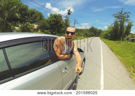 Young Happy Man Taking Selfie Picture with Smartphone on Monopod Stick. Hipster Making Road Trip Photo From Car Window